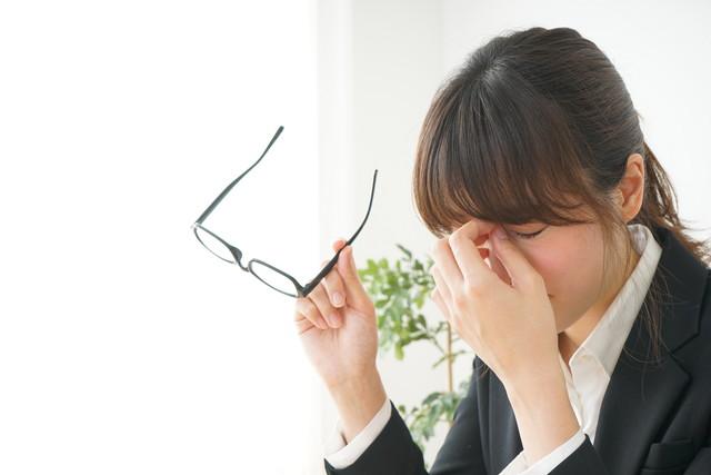 目頭を押さえる女性